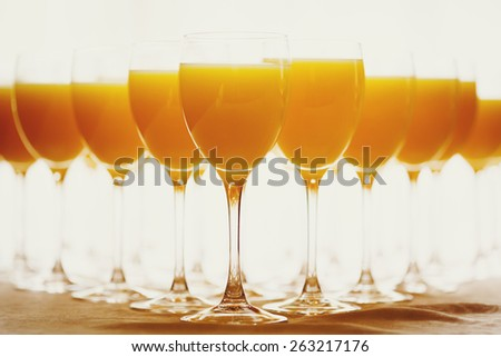 Row of Glasses with Fresh Orange Juice. Catering background. Selective focus, shallow DOF. Image toned in warm colors. - stock photo
