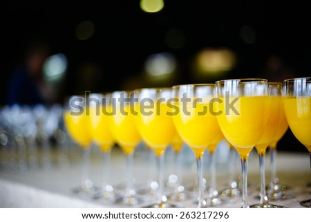Row of Glasses with Fresh Orange Juice. Catering concept. Bokeh blurred background. Selective focus, shallow DOF. - stock photo