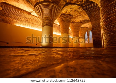Row of golden illuminated ancient brick columns and arches in basement support building