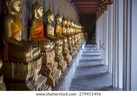Row of golden seated buddhas in front of decorative wall in a Buddhist temple in Bangkok Thailand - stock photo
