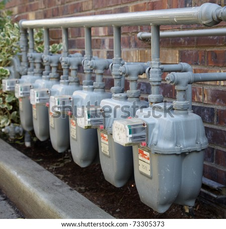 Row of gray gas meters at an apartment complex with complicated manifold piping
