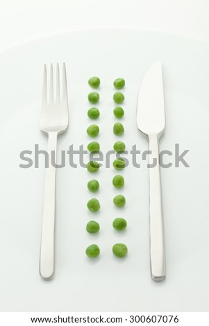Row of green peas with fork and knife