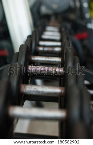 Row of Hand Barbells weight training equipment in gym room at Ranong , Thailand