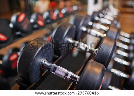 Row of heavy barbells in sports club