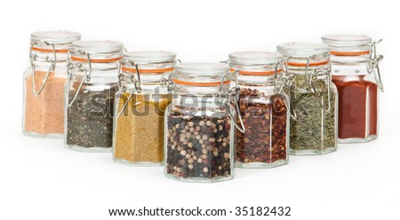 Row of herbs and spices in glass jars - stock photo