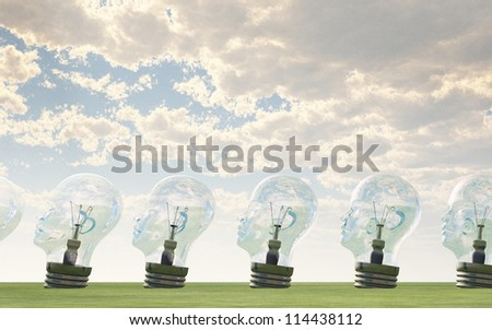 Row of human head light bulbs in landscape - stock photo