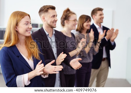 Row of impressed young business co-workers clapping a colleague as they stand in a line smiling and offering congratulations - stock photo