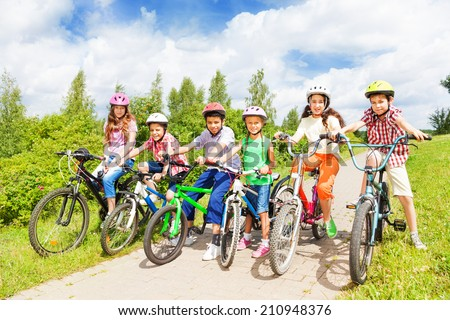 Row of kids diversity in helmets and bikes - stock photo