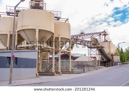 Row of large cylindrical metal tanks or silos at a refinery plant , mill or factory with an infrastructure of conveyor belts against a cloudy blue sky - stock photo