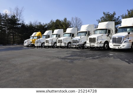 row of large tractor trailers ready for use - stock photo