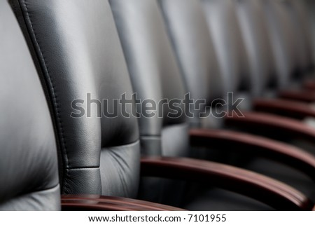 Row of leather black chairs in a boardroom