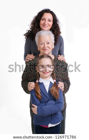 Row of little girl, grandmother, mother looking at camera in line on a white background - stock photo