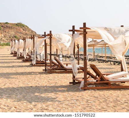 Row of luxurious beds on beach resort - stock photo