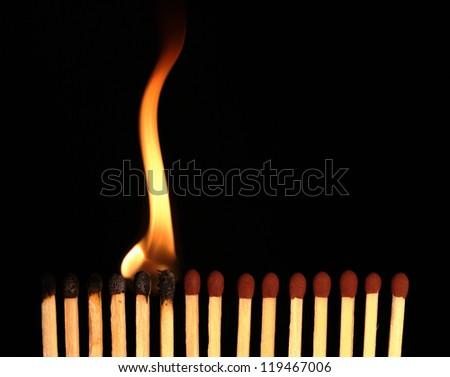 Row of matches starts burning, on black background - stock photo