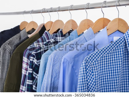 Row of men's clothes shirts on hangers - stock photo