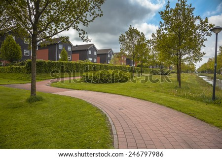 Row of Modern Middle Class Houses on an Ecological Managed Park with Selective Mowing Regime - stock photo
