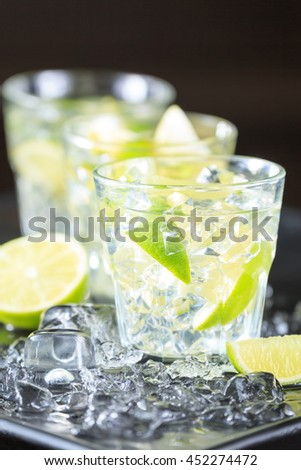 Row of mojito cocktails on a dark background with lime and ice. Fresh summer cocktail. Vertical