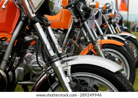 Row of motorbikes in a field - stock photo