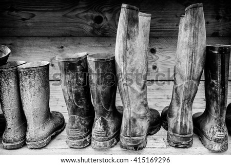 Row of muddy boots in front of a wooden wall - stock photo