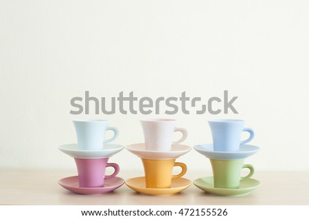 Row of multicolor coffee cups on wooden table.