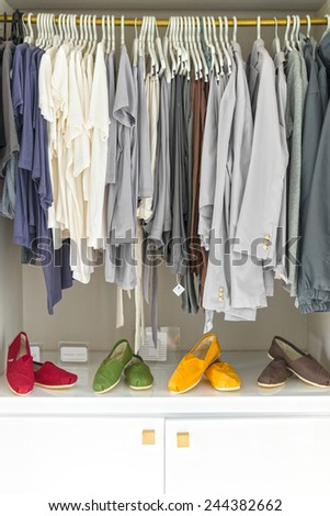 Row of new casual clothing on hangers at shop with four colorful pairs of shoes under it. Clothes presented as in wardrobe. Apparel ready for sale. Going shopping. Trade and commerce. - stock photo