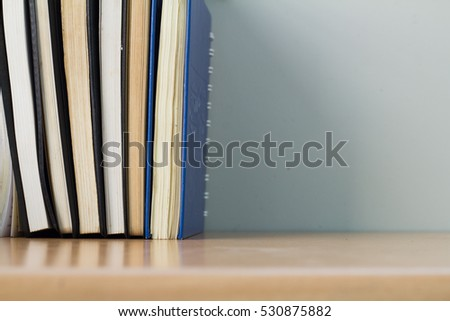 Row of old books on wooden desk