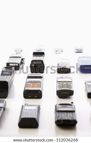 Row of old cell phones over white background