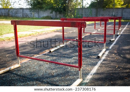 Row of old red hurdles for a hurdle race on abandoned stadium - stock photo