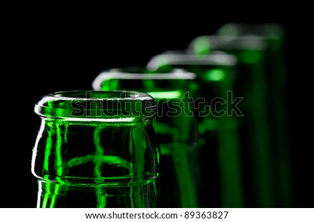 Row of open green beer bottles. Close-up view - stock photo