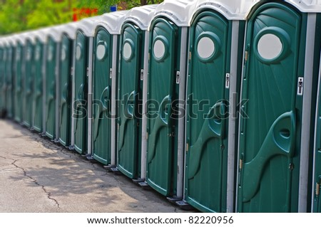 Row of outhouses or porta potties waiting to be used - stock photo