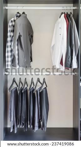 row of pants and shirts in wardrobe at home - stock photo