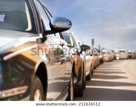 Row of parked cars with reflection of traffic and buildings - stock photo