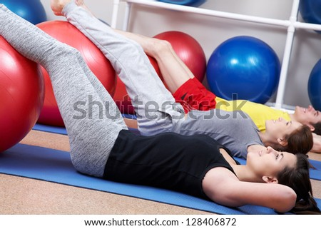 Row of people lying on mates with legs on balls - stock photo