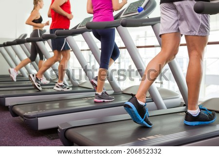 Row of people on treadmills at the gym - stock photo
