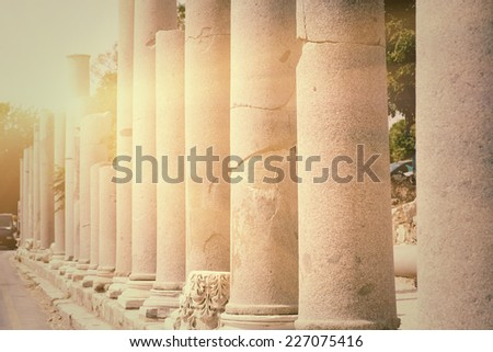 Row of pillars backlit in town Side (Turkey), ancient Roman architecture, ruins of aged castle, religious building in bright sun light, vintage photo - stock photo