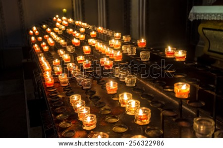 Row of red candle lights at altar in cathedral - stock photo