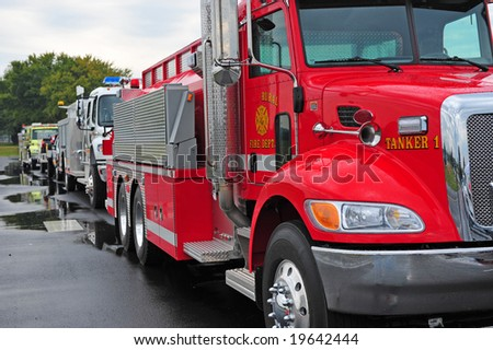 Row of rescue vehicles led by red fire truck - stock photo