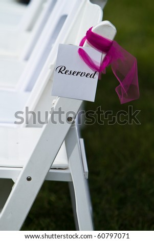 Row of reserved seats at an outdoor wedding ceremony - stock photo