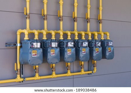 Row of residential natural gas meters and yellow pipe plumbing on exterior wall to measure household energy consumption - stock photo