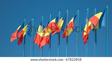 Row of Romanian flags against the blue sky.