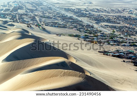 Row of sand dunes with a shantytown in the background at Huacachina, Peru - stock photo