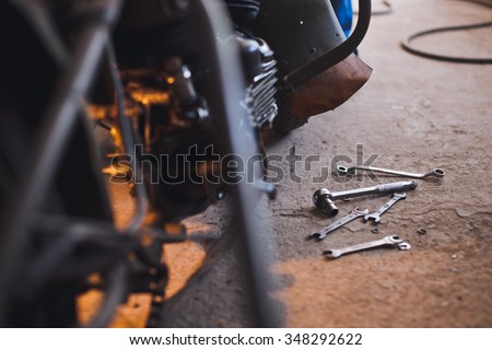 Row of screws and wrench tools on a floor in workshop near repaired old bike or motorcycle engine. Industrial scene with equipment on background and blurred foreground - stock photo