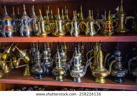 row of shiny traditional coffee pots and lamp at the souq in Dubai.