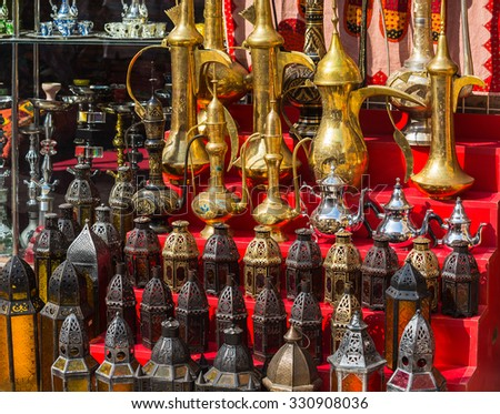 row of shiny traditional coffee pots and lamp at the souq in Dubai. - stock photo