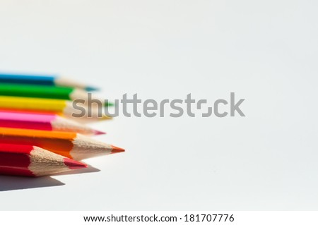 Row of Slanting colorful wooden crayons, macro with shallow dof. - stock photo