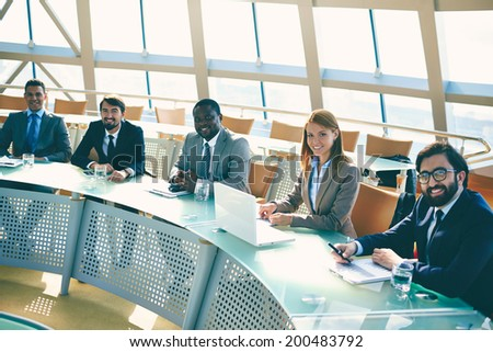 Row of smiling business people looking at camera at seminar - stock photo