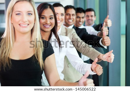 row of smiling business team giving thumbs up - stock photo