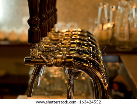 Row of stainless steel beer taps for dispensing draught beer from the metal storage kegs in a pub or bar at a nightclub - stock photo