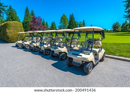 Row of the golf carts at the beautiful golf course in a sunny day. Canada, Vancouver. - stock photo