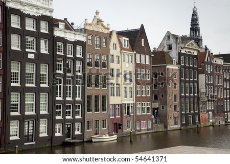 Row of the important old houses in amsterdam alongside a canal, with a church tower in the background - stock photo